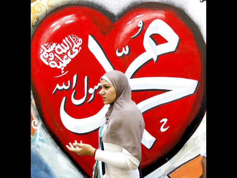 A woman walks past graffiti in support Prophet Muhammad along Mohamed Mahmoud Street near Tahrir Square in Cairo. The Arabic words read,