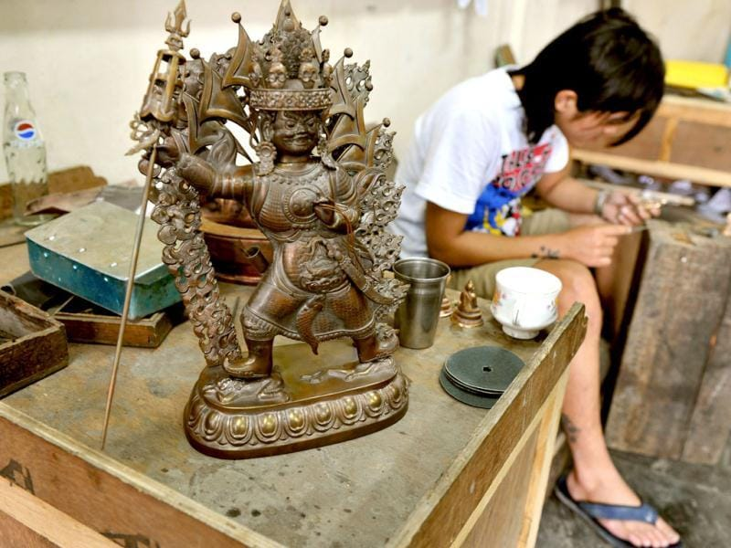 A traditional Tibetan craftsman hand sculpts a metal figurine of the Buddha at the Norbulingka Institute near Dharamshala. The Norbulingka Institute is a centre for arts dedicated to the preservation of Tibetan art and culture. (AFP Photo)