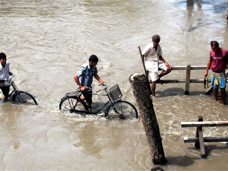 Villagers wades through the flood water at Kanikuch under Kamrup district in Assam. PTI Photo