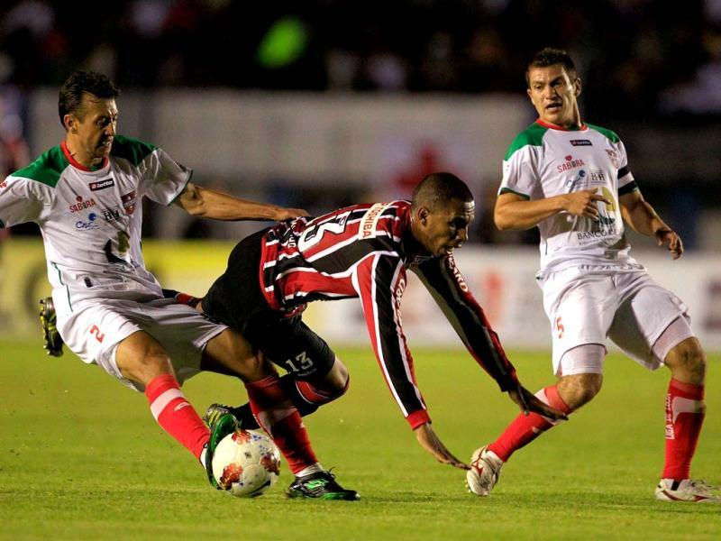 Brazil's Sao Paulo's Paulo Miranda, center, is tackled by Ecuador's Liga Deportiva Universitaria's Arnaldo Vera during a Copa Sudamericana soccer match in Loja, Ecuador. At right, Ecuador's Liga Deportiva Universitaria's Pedro Larrea. AP Photo
