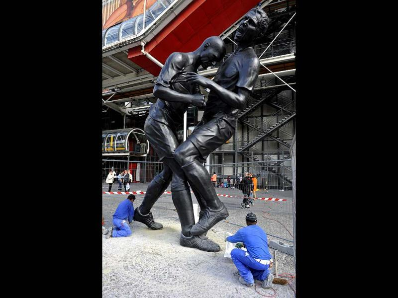 Employees work in Paris near a bronze sculpture by Algerian artist Adel Abdessemed displayed in front of the Centre Pompidou contemporary art center, aka Beaubourg. The sculpture immortalizes the