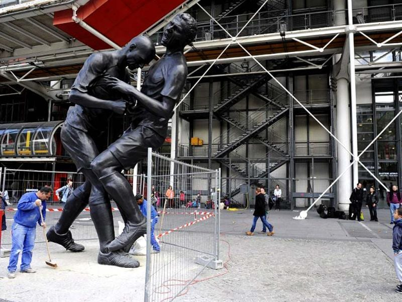 Employees sweep in Paris near a bronze sculpture by Algerian artist Adel Abdessemed displayed in front of the Centre Pompidou contemporary art center, aka Beaubourg. The sculpture immortalizes the
