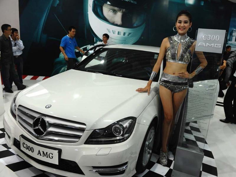 A model stands next to a German car maker Mercedes Benz's sedan C300 AMG during the Vietnam Motorshow 2012 being held in Hanoi. AFP/Hoang Dinh Nam
