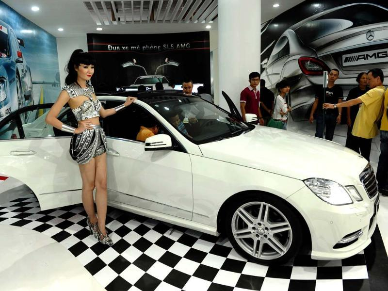 A model stands next to a German car maker Mercedes Benz' s sedan E300 AMG during the Vietnam Motorshow 2012 being held in Hanoi. AFP/Hoang Dinh Nam