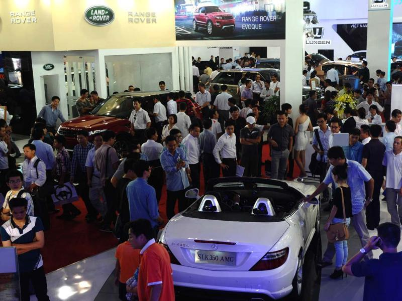 Visitors look at a Mercedes Benz SLK 350 AMG and a Land Rover Range Rover during the Vietnam Motorshow 2012 being held in Hanoi. AFP/Hoang Dinh Nam