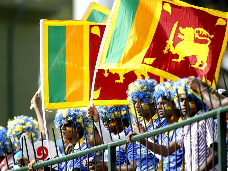 Sri Lankan cricket fans wave flags as they cheer for their team during the ICC Twenty20 Cricket World Cup Super Eight match in Pallekele. (AP Photo/Aijaz Rahi)