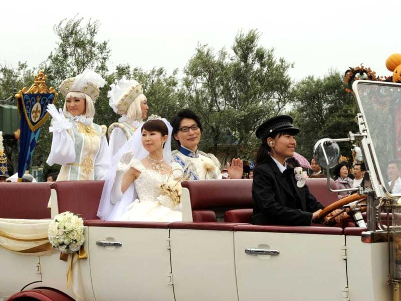 Newly wed bride Mayumi Kagoshi and her groom Takayuki Abiko wave from a limousine during their wedding procession at the Tokyo Disneyland in Urayasu, suburban Tokyo. AFP photo