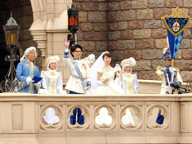 Bride Mayumi Kagoshi and her groom Takayuki Abiko wave from the balcony of the Cinderella castle after their wedding at the castle of the Tokyo Disneyland in Urayasu, suburban Tokyo. AFP photo