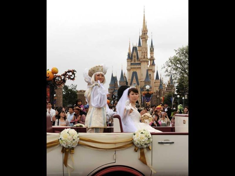 Bride Mayumi Kagoshi and her groom Takayuki Abiko ride a limousine past the Cinderella castle (back) during their wedding procession at the Tokyo Disneyland in Urayasu, suburban Tokyo. Abiko and Kagoshi became the first couple to hold a wedding ceremony in Disney's theme park in Japan. AFP photo