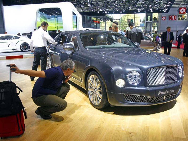 A member of the media looks at a Bentley Mulsanne, on the eve of the opening of the Paris Auto Show. AP Photo/Remy de la Mauviniere