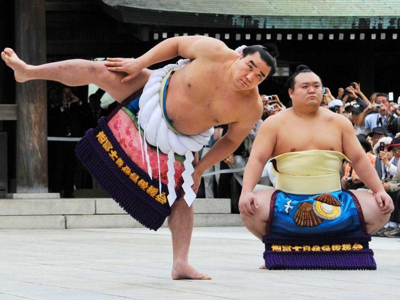 Accompanied by sumo wrestler Takarafuji (R), new yokozuna, or grand champion, Harumafuji performs the ceremonial entrance into the ring at Meiji Shrine in Tokyo. The Mongolian sumo wrestler was promoted to the highest rank 'yokozuna'.   AFP PHOTO / Rie ISHII