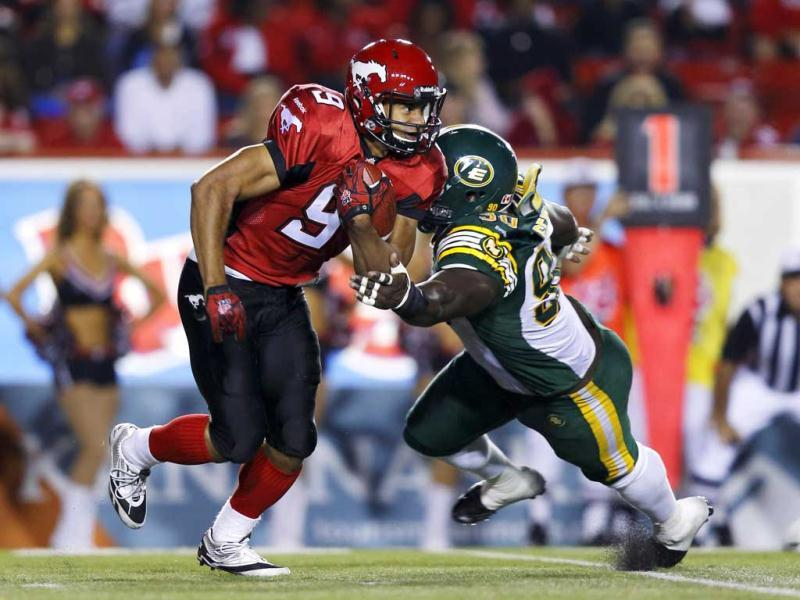 Calgary Stampeders Jon Cornish (L) gets past Edmonton Eskimos Almondo Sewell during the first half of their CFL football game in Calgary, Alberta. Reuters Photo