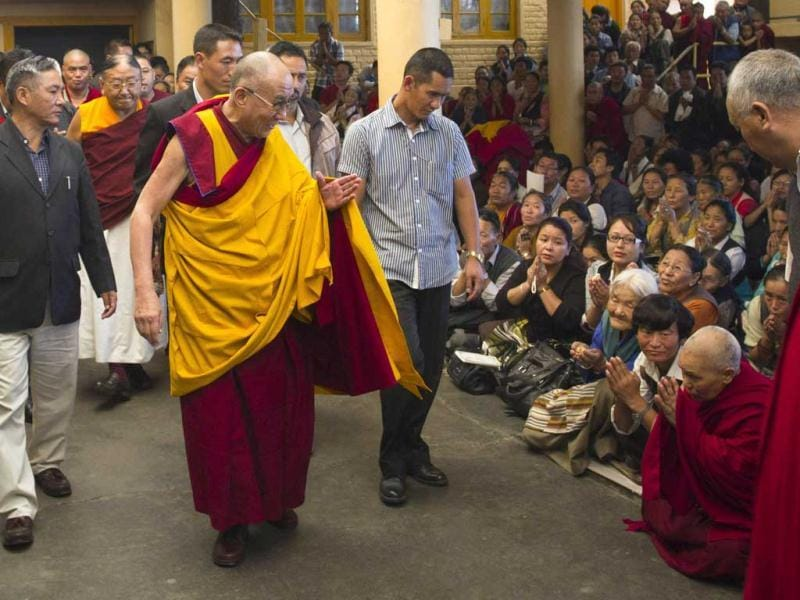 Dalai Lama greets devotees as he leaves after leading a prayer ceremony for Tibetans who have self-immolated since last year, at the Tsuglakhang temple in Dharmsala. AP Photo