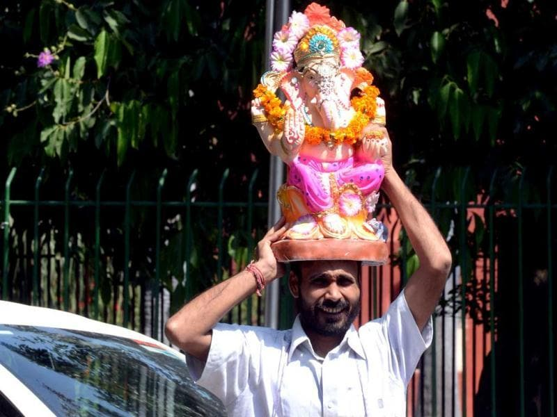A devotee carries an idol of Lord Ganesha for immersion through the streets of New Delhi. AFP photo