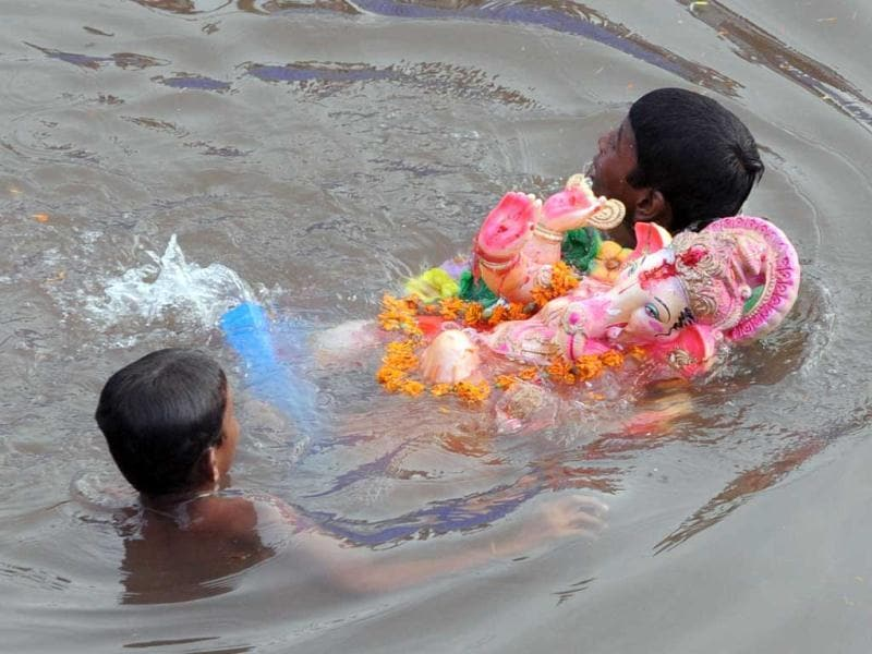 Devotees swim with an idol of Lord Ganesha in an artificial pond, dug for the ongoing Ganesh Chathurthi festival to help control pollution and waste, along the banks of the Sabarmati river in Ahmedabad. AFP photo