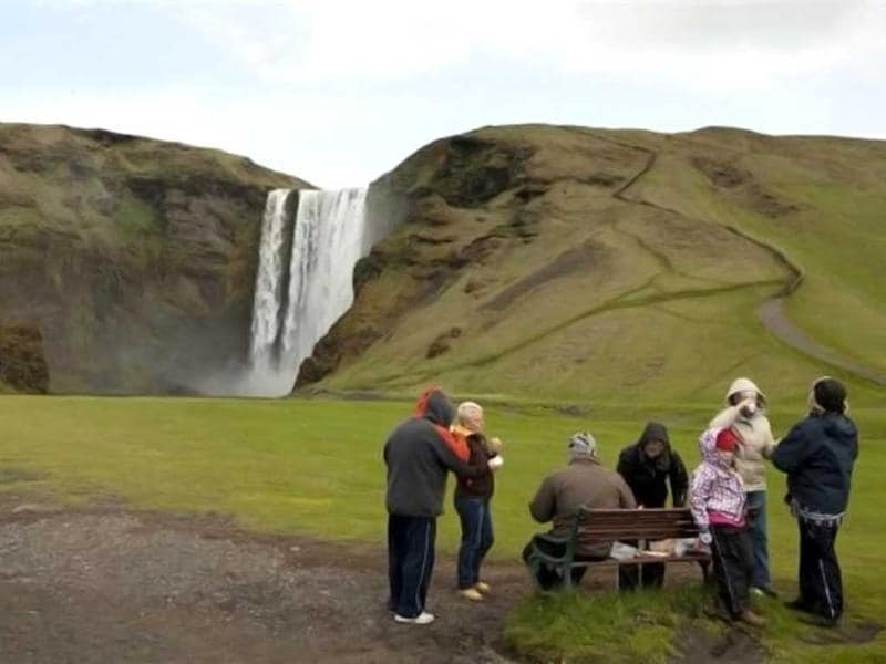 A group of tourists eats a picnic lunch in front of a waterfall in Skogarfoss, Iceland. Reuters/Lucas Jackson