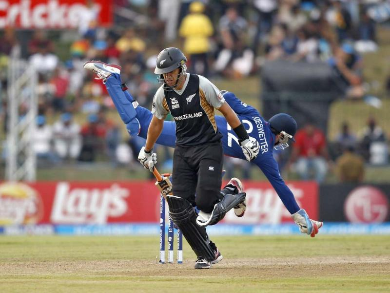 England's wicketkeeper Craig Kieswetter dives to catch the ball as New Zealand's captain Ross Taylor (front) runs between the wickets during their Twenty20 World Cup Super 8 cricket match in Pallekele. (Reuters/Dinuka Liyanawatte)