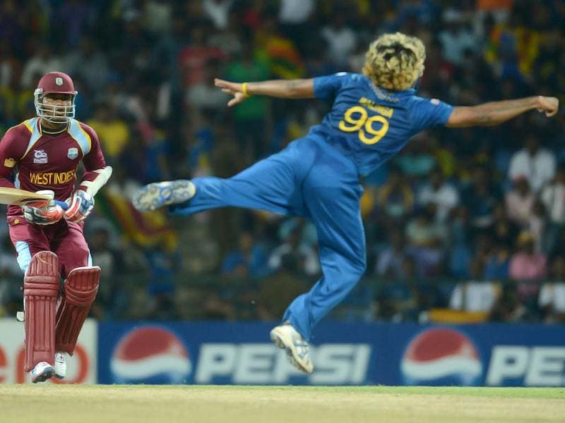 West Indies cricketer Marlon Samuels (L) watches as Sri Lanka bowler Lasith Malinga (R) dives in vain to stop a shot during the ICC Twenty20 Cricket World Cup's Super Eight match between Sri Lanka and West Indies at the Pallekele International Cricket Stadium in Pallekele. AFP Photo/Prakash Singh