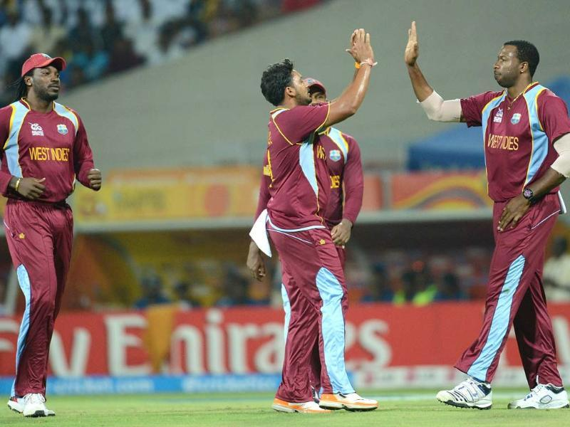 West Indies bowler Ravi Rampaul (C) celebrates after taking the wicket of unseen Sri Lankan batsman Tillakaratne Dilshan with teammates Chris Gayle (L) and Kieron Pollard (R) during the ICC Twenty20 Cricket World Cup's Super Eight match between Sri Lanka and West Indies in Pallekele. AFP Photo/Prakash Singh