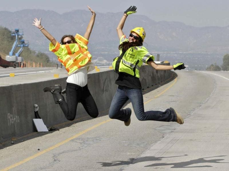 Construction officials Kasey Shula (L) and Natasha Jones pose for a photo on the 405 Freeway as construction crews demolish a portion of the Mulholland Drive bridge along the 405 Freeway in Los Angeles. AFP Photo