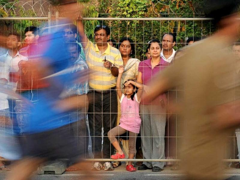 A young girl watches as runners participate in the 2012 Airtel Delhi Half Marathon in New Delhi. AFP Photo