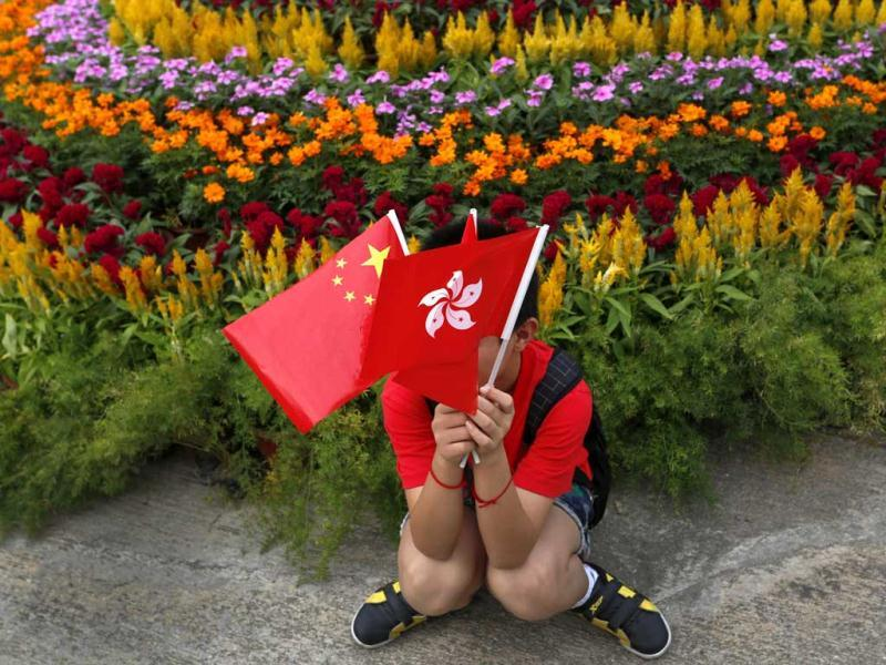 A boy from mainland China poses with a Chinese national flag, left, and a Hong Kong flag at the venue of a flag-raising ceremony celebrating China's National Day in Hong Kong. AP Photo