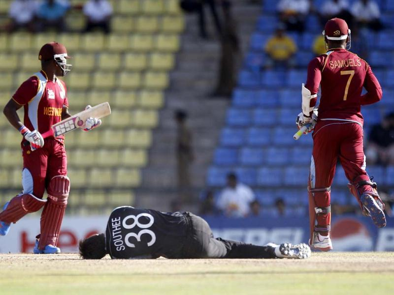 New Zealand's bowler Tim Southee, center, falls on the ground in an attempt to stop the ball as West Indies' batsmen Darren Bravo, left, and Marlon Samuels run between the wickets to add runs during their ICC Twenty20 Cricket World Cup Super Eight match in Pallekele. (AP Photo/Aijaz Rahi)