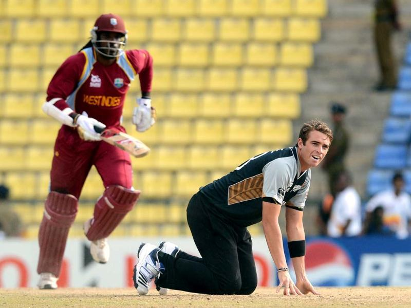 New Zealand cricketer Tim Southee (R) makes an unsuccessful attempt to field the ball as West Indies cricketer Chris Gayle takes a run during the ICC Twenty20 Cricket World Cup's Super Eight match between New Zealand and West Indies at the Pallekele International Cricket Stadium in Pallekele . AFP Photo/Prakash Singh