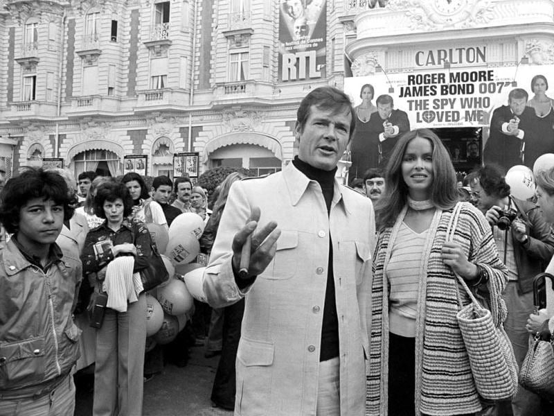 In this May 20, 1977 file photo, actor Roger Moore, alias British secret agent James Bond, is accompanied by co-star Barbara Bach as they arrive for the screening of their latest 007 feature,