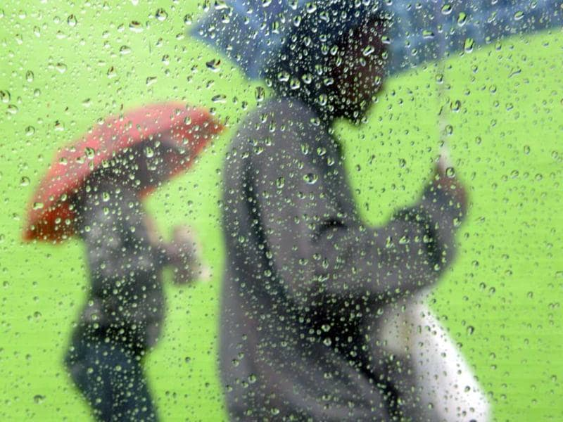 Passersby walk through the rain with umbrellas on Redwood Avenue in Paterson, New Jersey. (AP Photo)