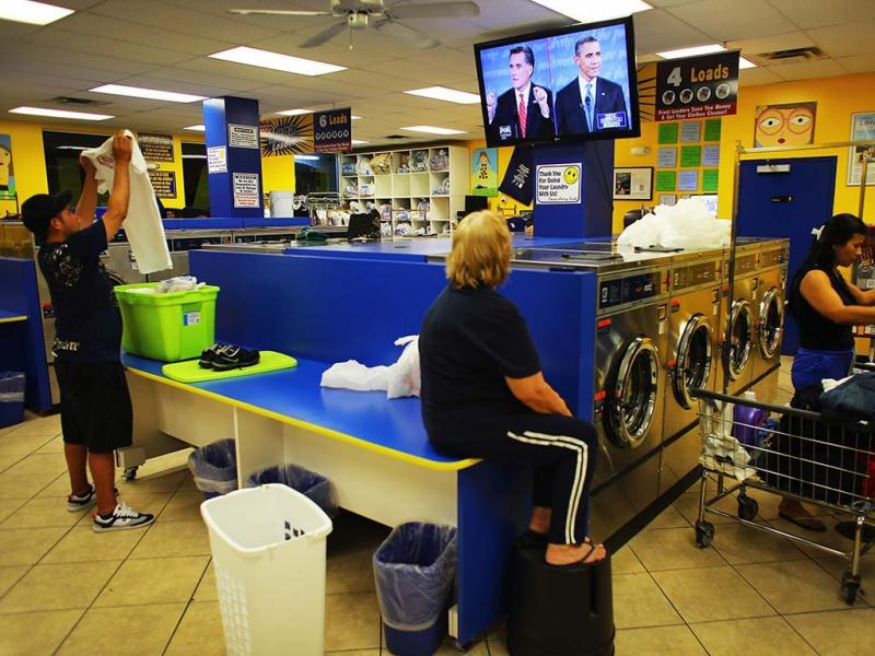 People at the Lavanderia coin laundry watch as US President Barack Obama and Republican presidential candidate and former Massachusetts Governor Mitt Romney are seen during their televised debate in Miami, Florida. (AFP Photo)