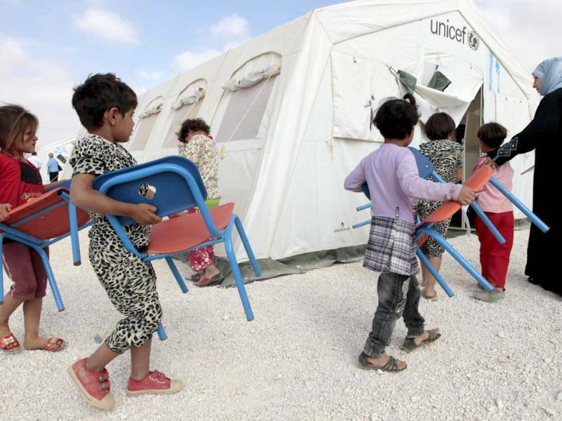 Young Syrian refugees carry their chairs into a classroom at a UNICEF-run school in the al-Zaatari refugee camp in the Jordanian city of Mafraq near the border with Syria. The school is a grant from the European Union to provide education to Syrian refugees residing in Jordan. AFP/Khalil Mazraawi
