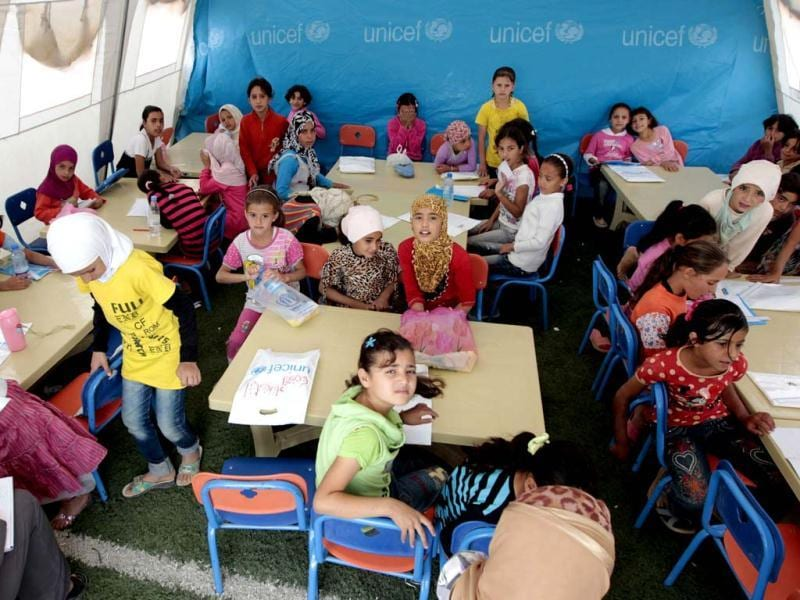Young Syrian refugees sit at a UNICEF-run school in the al-Zaatari refugee camp in the Jordanian city of Mafraq near the border with Syria. The school is a grant from the European Union to provide education to Syrian refugees residing in Jordan. AFP/Khalil Mazraaw