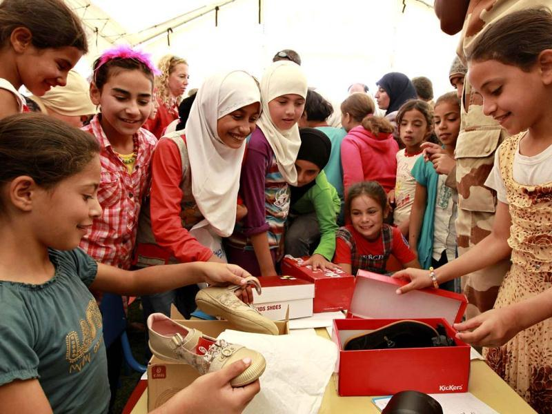 Syrian child refugees look at gifts from Corinne Breuze, French ambassador to Jordan, and Dominique Hyde, director of UNICEF in Jordan, during the official opening of the first school at Al Zaatri refugee camp, in the Jordanian city of Mafraq, near the border with Syria. Reuters/Muhammad Hamed