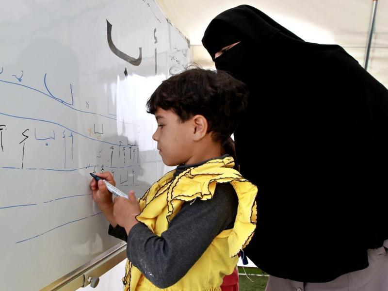 A Syrian child refugee writes on a whiteboard during her fourth day of school at Al Zaatri refugee camp, in the Jordanian city of Mafraq, near the border with Syria. The school is a grant from the European Union to provide education to Syrian refugees residing in Jordan. Reuters/Muhammad Hamed