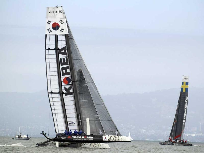 Team Korea, left, races against Artemis Racing White of Sweden, right, during their quarterfinal match race of the America's Cup World Series sailing event in San Francisco. Artemis Racing White won their race. (AP Photo)