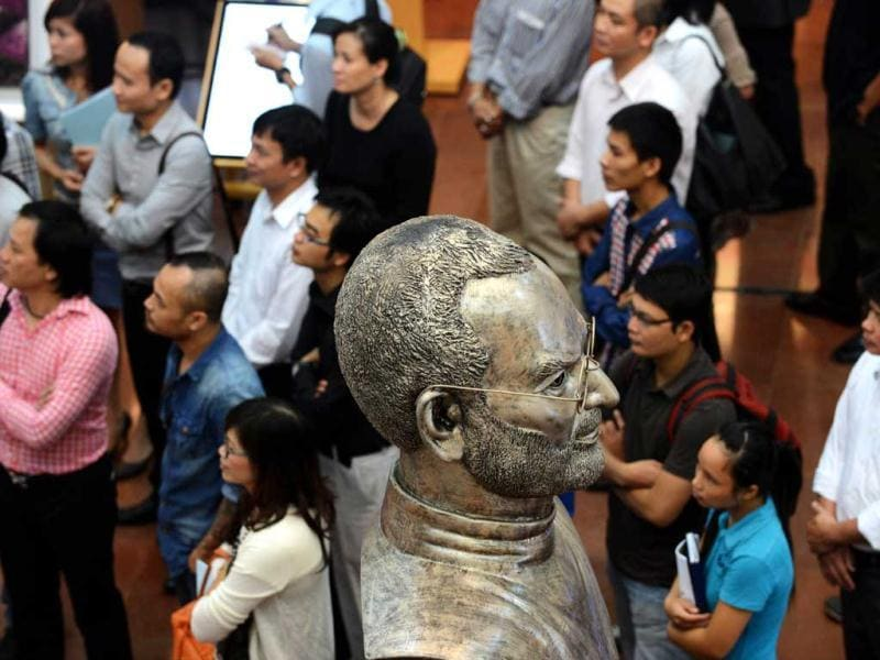 A bust of Steve Jobs looms over visitors at the opening ceremony of at an art exhibition in commemoration of the late Apple's co-founder Steve Jobs on the occasion of his first death anniversary in Hanoi. AFP Photo/Hoang Dinh Nam