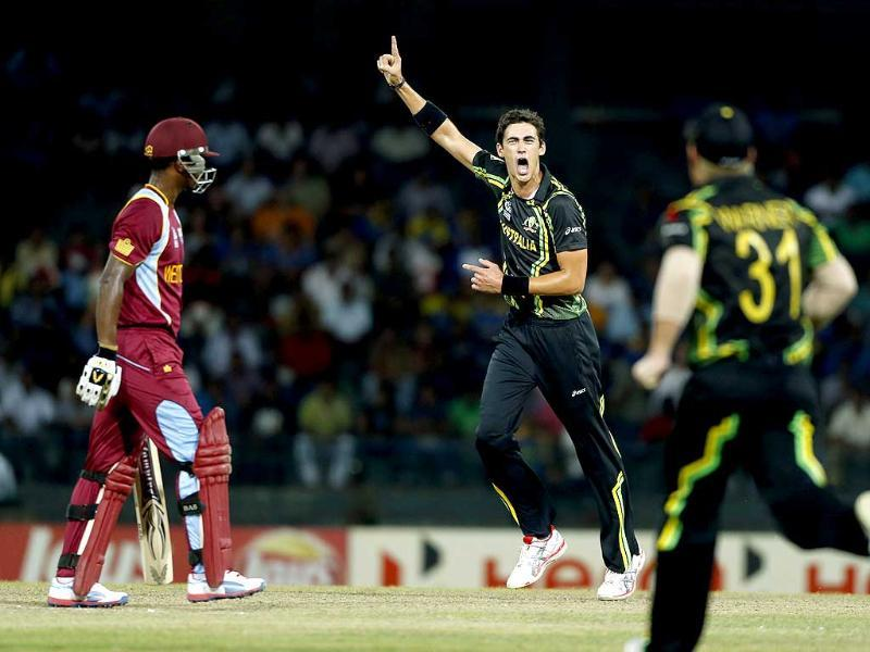 Australia bowler Mitchell Starc (2R) celebrates after taking the wicket of West Indies batsman Johnson Charles, left, during the ICC Twenty20 Cricket World Cup semi final match in Colombo. AP Photo/Eranga Jayawardena