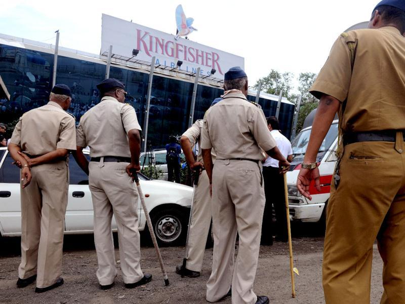 Policemen watch as striking employees of Kingfisher Airlines protest outside the company's office during a protest march in Mumbai. AFP / Indranil Mukherjee