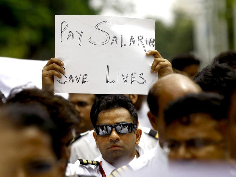 A Kingfisher Airlines employee holds a placard during a protest outside the domestic airport in Mumbai. (AP /Rafiq Maqbool)