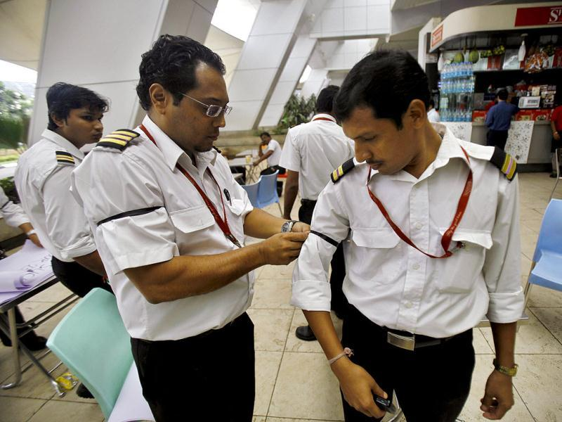 Kingfisher Airlines employees wear black arm bands during a protest outside the domestic airport in Mumbai. (AP /Rafiq Maqbool)