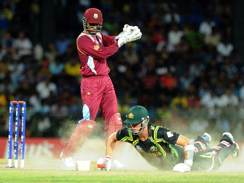 Australian cricketer Pat Cummins runs between the wickets as West Indies cricketer Samuel Badree as West Indies wicketkeeper Denesh Ramdin (L) looks on during the ICC Twenty20 Cricket World Cup's semi-final match in Colombo. AFP Photo/Ishara S. Kodikara