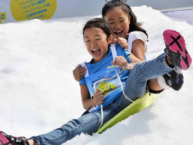 Young girls ride a sledge on a snow slope at a hotel in Tokyo. The hotel carried 25 tons of artificial snow from their Naeba ski resort on the first day of three consecutive autumn holidays for the promotion of the ski resort. (AFP photo/Yoshikazu Tsuno)