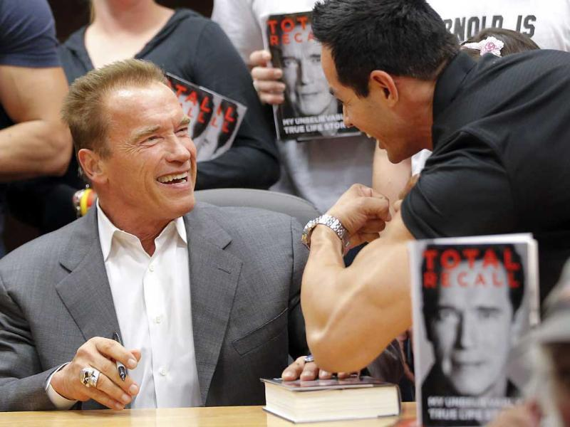 A man flexes his muscles for former California Governor Arnold Schwarzenegger during a book signing event for his book