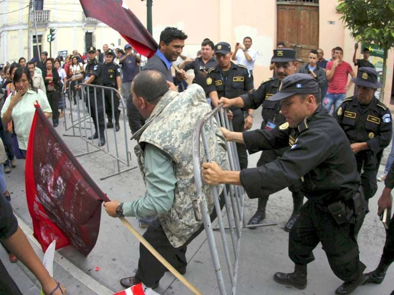 Protesters push against a security fence set up by the police as they take part in a demonstration outside the Casa Presidencial, or Presidential House, in Guatemala City. (Reuters/Jorge Dan Lopez)