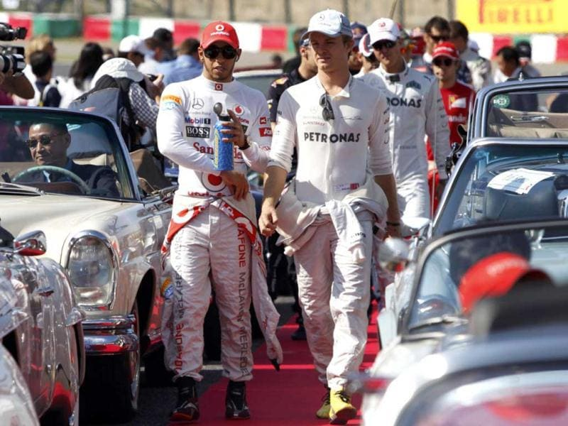 McLaren Formula One driver Lewis Hamilton (L) of Britain walks beside Mercedes Formula One driver Nico Rosberg of Germany before the drivers' parade of the Japanese F1 Grand Prix at the Suzuka circuit. Reuters/Issei Kato