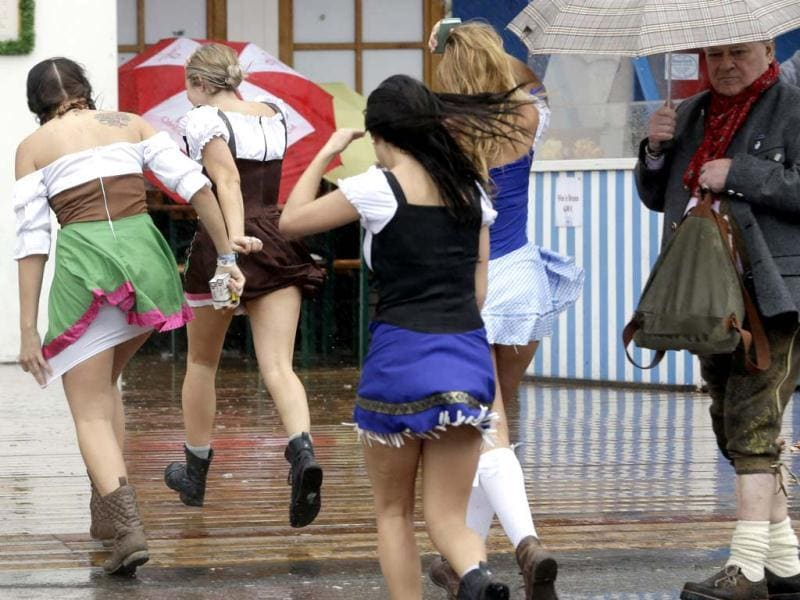 Young women try to cover from heavy rain at the last day of the famous Bavarian Oktoberfest beer festival in Munich. AP Photo