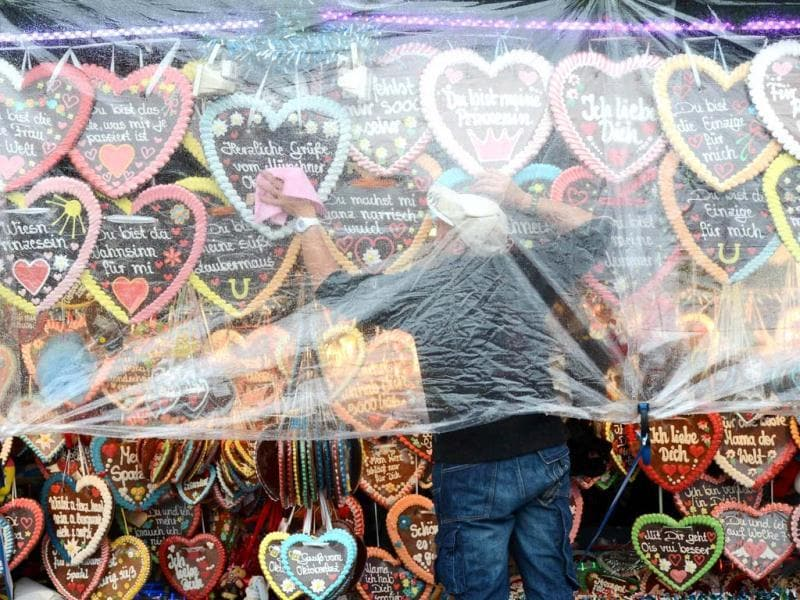 A man wipes gingerbread hearts after the rain at a booth of the Oktoberfest festival fair ground at the Theresienwiese in Munich. AFP Photo