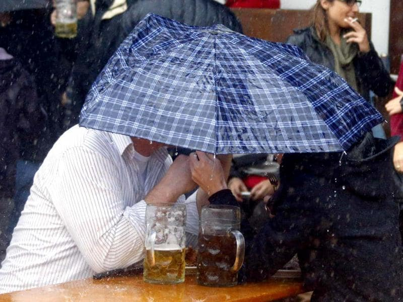 Oktoberfest visitors sit under an umbrella during heavy rain at the last day of the world biggest beer festival in Munich. Reuters Photo
