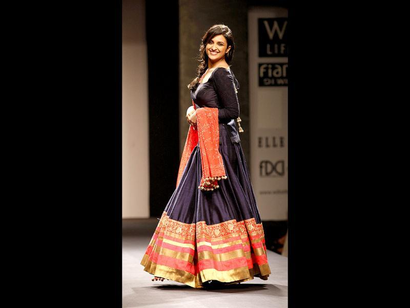 Clad in a beautiful navy blue-orange lehenga, teamed with a deep-cut choli and a heavy dupatta, chirpy and spontaneous actress Parineeti Chopra left the audience applauding and cheering when she walked the ramp for veteran designer Manish Malhotra at the ongoing Wills Lifestyle India Fashion Week. (Photo: Raj K Raj/ Hindustan Times)